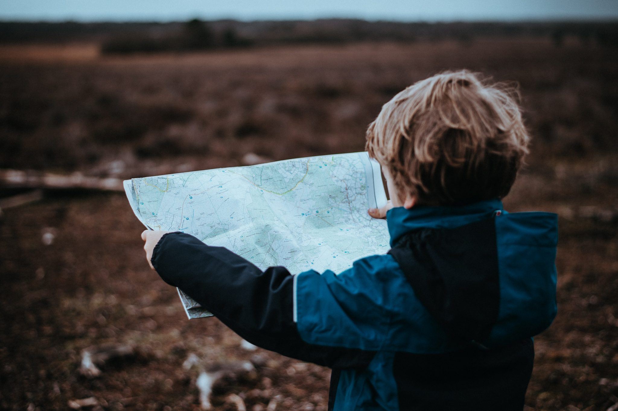 Image of a child standing outside looking at a map.